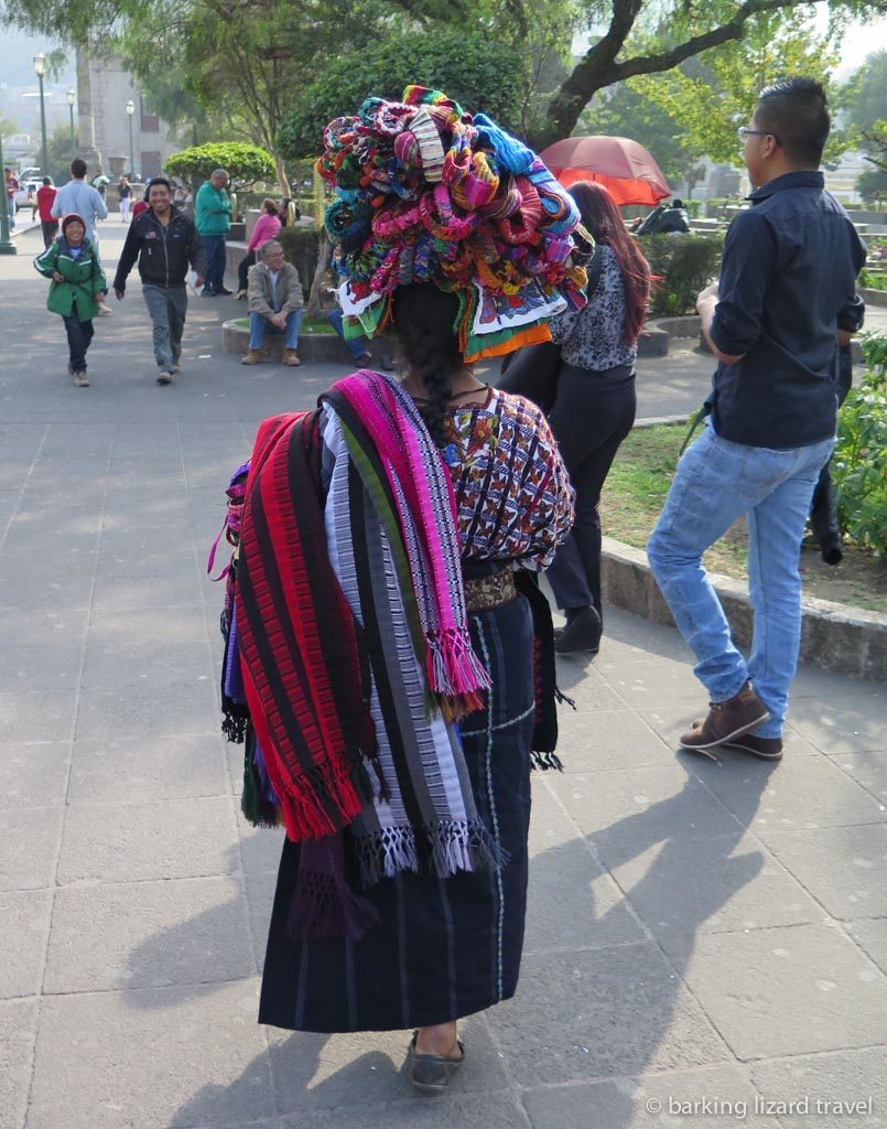 A guatemalan woman in traditional clothes selling textiles in quetzaltenango