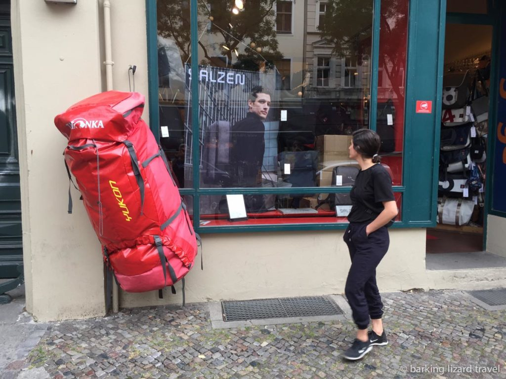 An oversized red backpack hanging up outside a shop. A women in black clothes is walking by