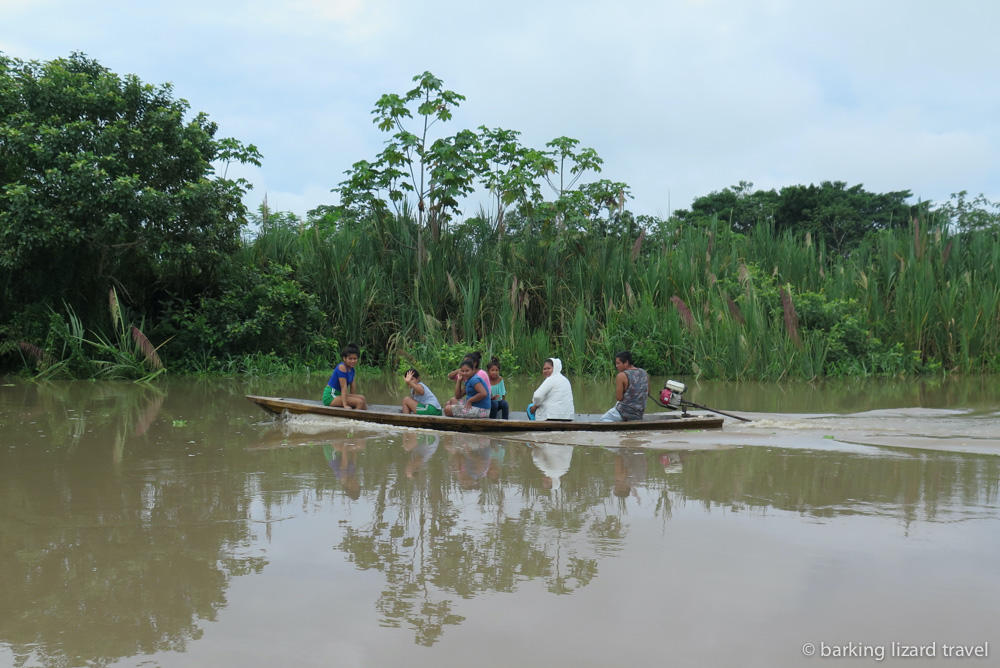 photo of small wooden motor boat with amazon villagers in it